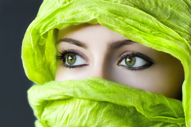 Closeup of the eyes of a woman with a green hijab under the lights Free Photo