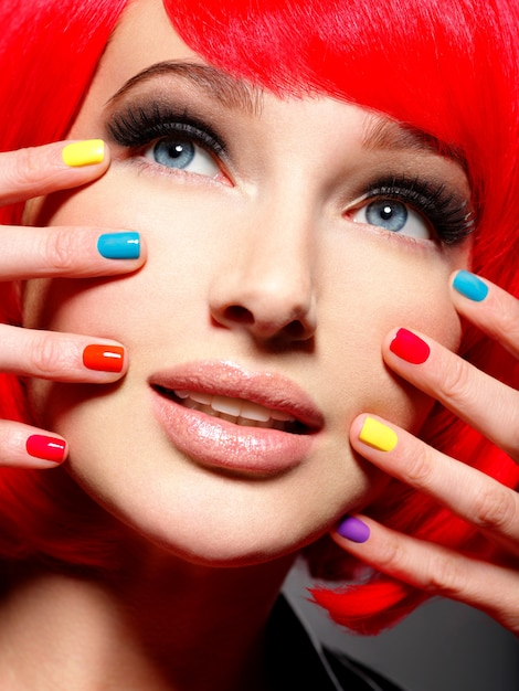 明るい多色の爪を持つ美しい少女のクローズアップの顔。 無料写真
