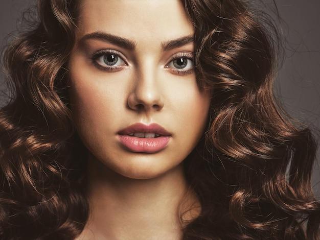 연기가 자욱한 눈 화장과 아름 다운 여자의 근접 촬영 얼굴. 긴 곱슬 머리를 가진 섹시하고 화려한 갈색 머리 여자. 포즈를 취하는 매력적인 여성의 초상화입니다. 무료 사진