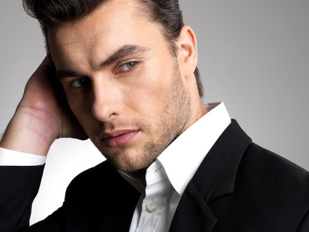 スタジオで黒のスーツのカジュアルなポーズでファッション青年実業家のクローズアップの顔 無料写真