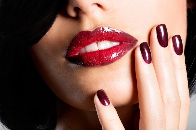 아름다운 섹시한 붉은 입술과 어두운 손톱을 가진 여자의 근접 촬영 얼굴 무료 사진