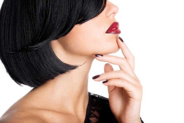 美しいセクシーな赤い唇と暗い爪を持つ女性のクローズアップの顔 無料写真