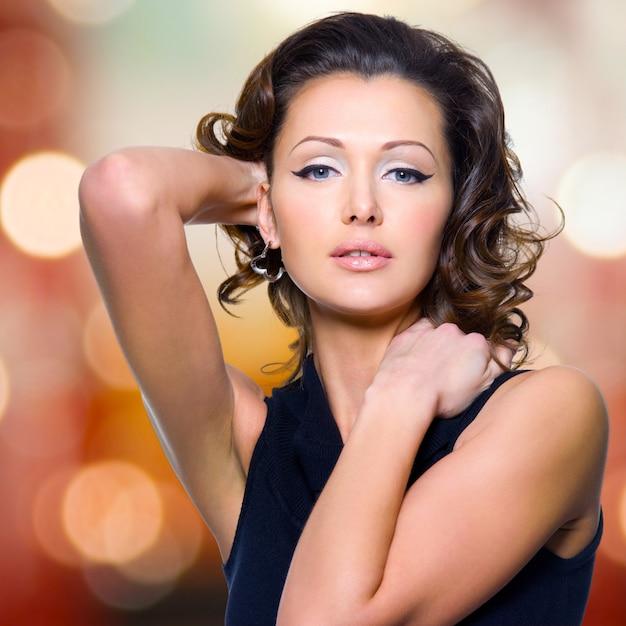 長い巻き毛のポーズで美しい大人の女性のクローズアップ顔 無料写真