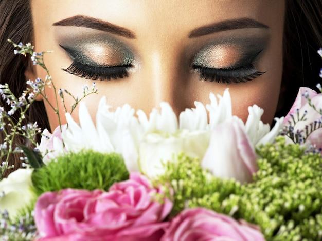 꽃과 함께 아름 다운 여자의 근접 촬영 얼굴입니다. 젊은 매력적인 여자 보유 봄 꽃의 꽃다발 무료 사진