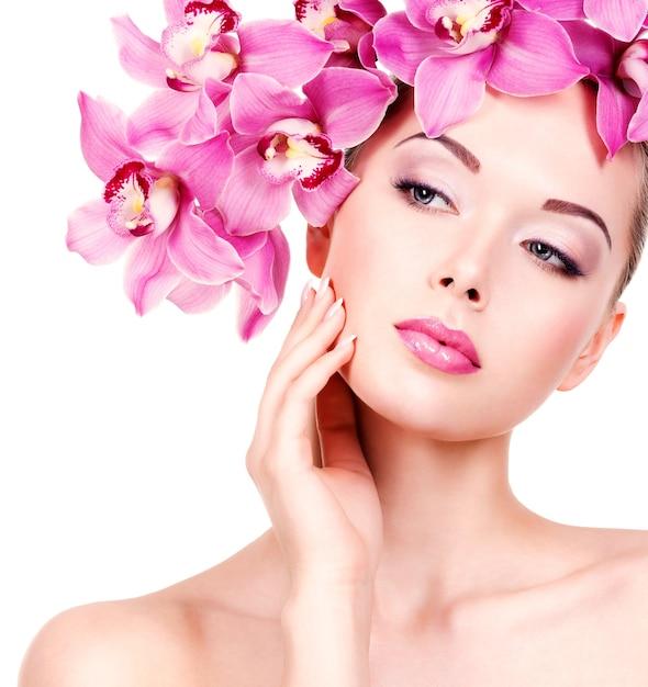 Fronte del primo piano di una giovane donna bellissima con un trucco occhi viola e labbra. bella ragazza adulta con fiore vicino al viso. - isolato su sfondo bianco Foto Gratuite