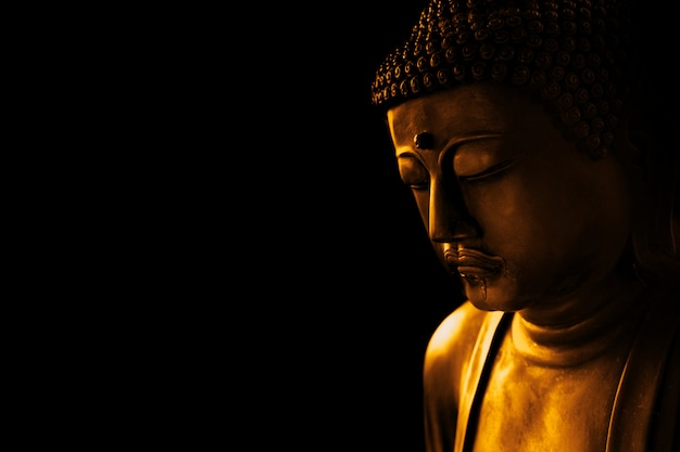 Closeup face of zen stone art buddha in dark for background asian way tranquil of meditation and religious. Premium Photo