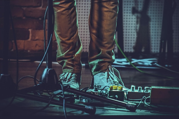 Closeup of the feet of a person near guitar pedals and a mic stand under the lights Free Photo
