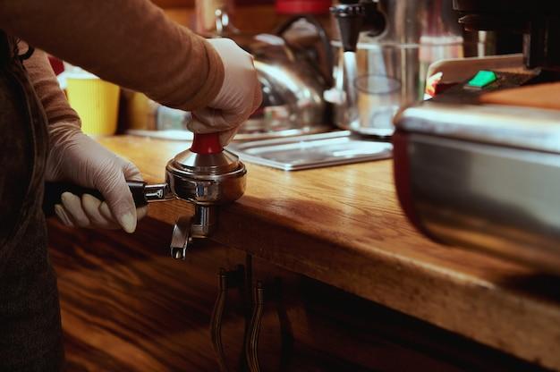 Closeup of female barista's hands tempering, pressing ground coffee in metal portafilter. tamping coffee Premium Photo