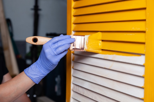 Closeup female hand in purple rubber glove with paintbrush painting natural wooden door with yellow paint.  creative design house interior. how to paint wooden surface. selected focus Premium Photo