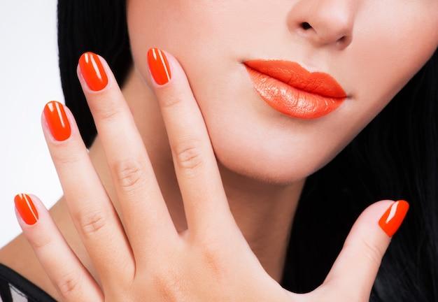 Primo piano mano femminile con belle unghie di colore arancione sul viso della donna Foto Gratuite