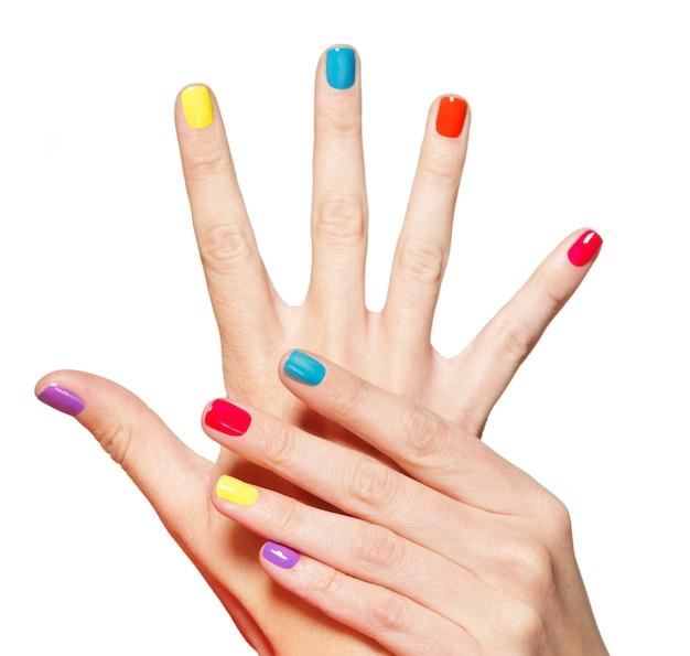 흰색 위에 여러 가지 빛깔의 손톱 근접 촬영 여성 손. 무료 사진