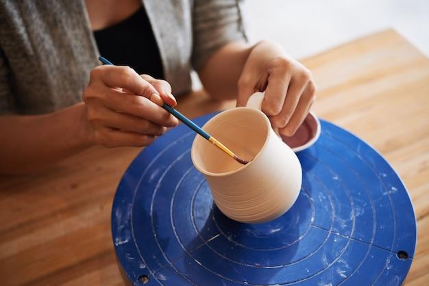 Closeup of female hands decorating a handmade clay mug Free Photo