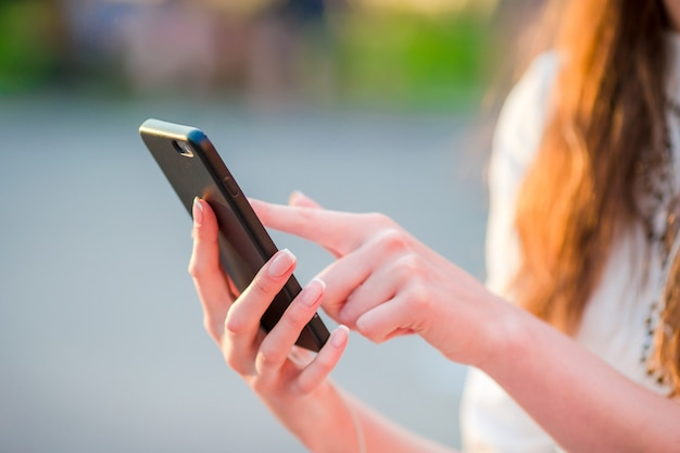 Closeup of female hands is holding cellphone outdoors on the street in evening lights. woman using mobile smartphone. Premium Photo