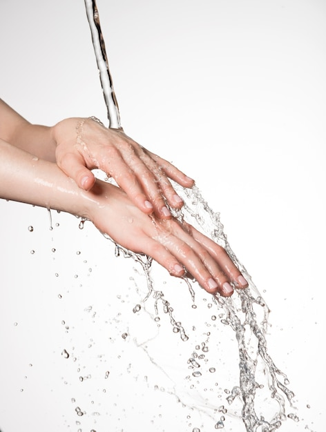 Closeup female hands under the stream of splashing water - skin care concept Free Photo