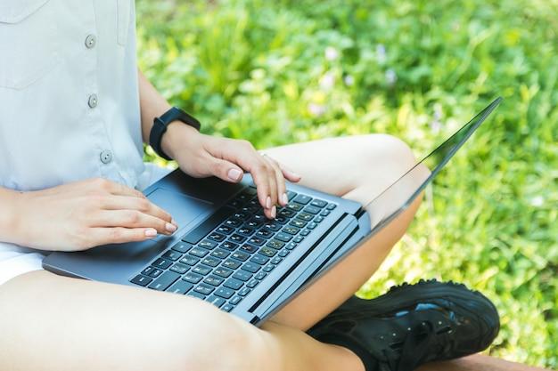 Крупным планом женские руки работают или учатся онлайн на ноутбуке в парке и наслаждаясь время в одиночестве в природе Premium Фотографии