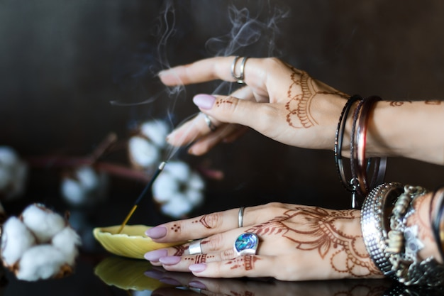 Closeup of female wrists painted with henna traditional indian oriental mehndi ornaments. hands dressed in bracelets and rings put aromatic stick in stand.  branch with cotton flowers on background. Premium Photo
