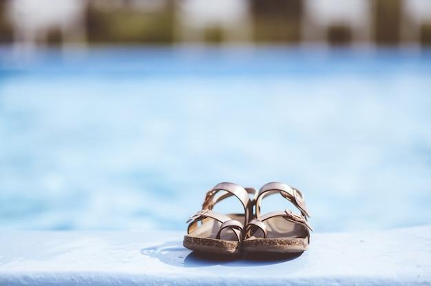 Снимок крупным планом кожаных сандалий, лежащих у бассейна Бесплатные Фотографии