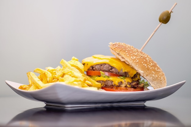 Closeup of french fries and a burger in a plate under the lights against a white wall Free Photo