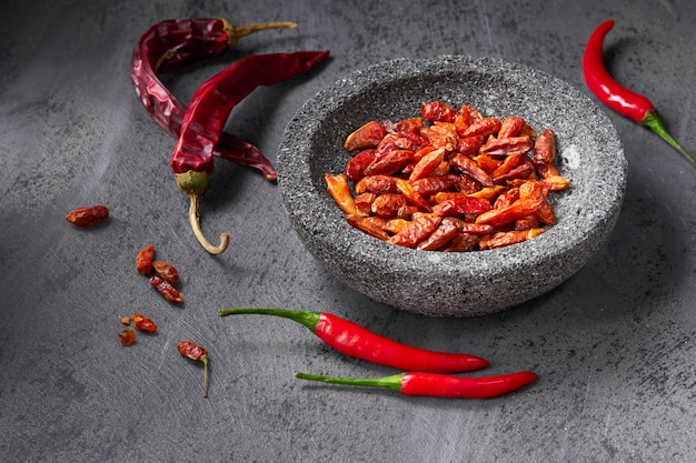 Closeup on  fresh hot chili peppers on dark textured table and dry ones in stone bowl Premium Photo