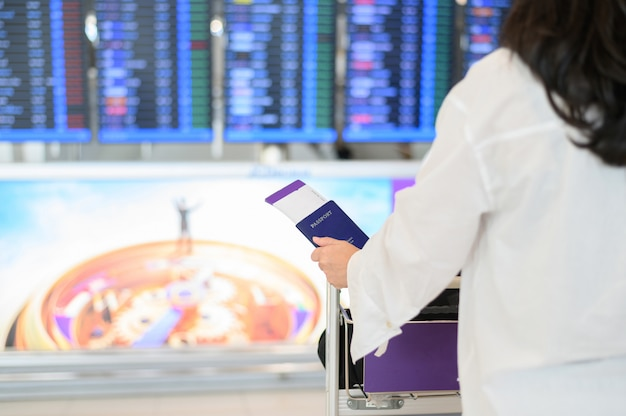 Closeup of girl holding passports and boarding pass at airport Premium Photo
