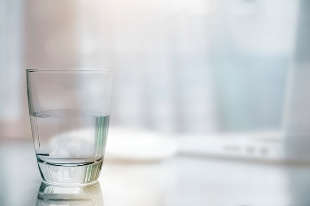 Closeup glass of clean water on white table with blurred image of laptop and mouse background. Premium Photo