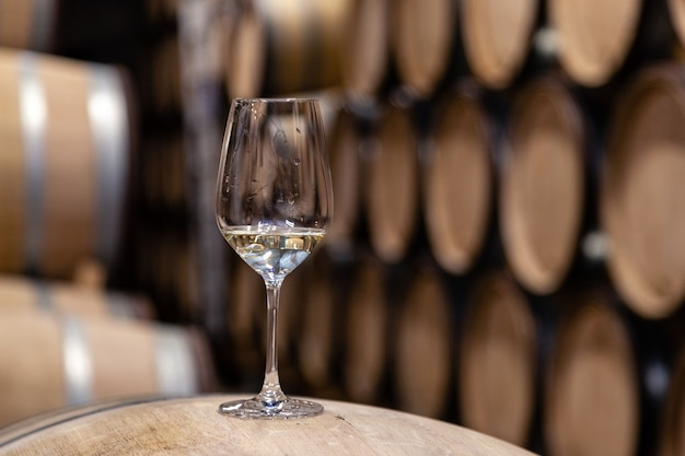 Closeup glass with white wine on background wooden wine oak barrels stacked in straight rows in order, old cellar of winery, vault. Premium Photo