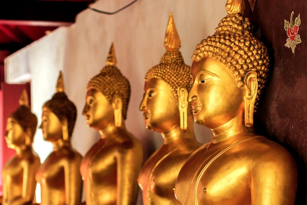 Closeup golden buddha with soft-focud and over light in the background Premium Photo
