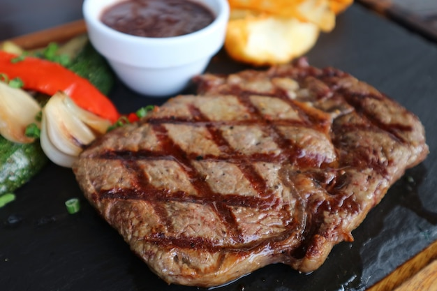 Closeup grilled ribeye steak with red wine sauce served on hot stone plate Premium Photo
