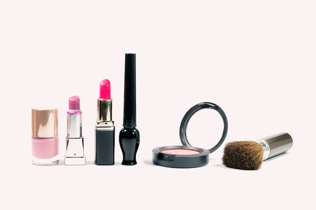 Closeup group of makeup cosmetics on white background. Premium Photo