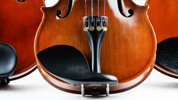 Closeup half front side of wooden violin put on background,show detail and part of violin Premium Photo