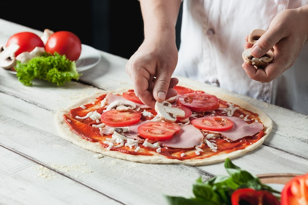 Closeup hand of chef baker in white uniform making pizza at kitchen Free Photo