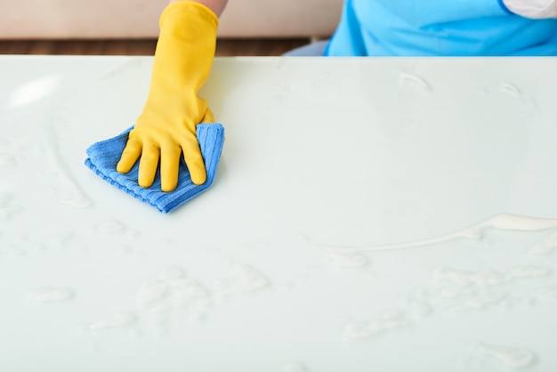 Closeup of hand in glove cleaning table with foam detergent Free Photo
