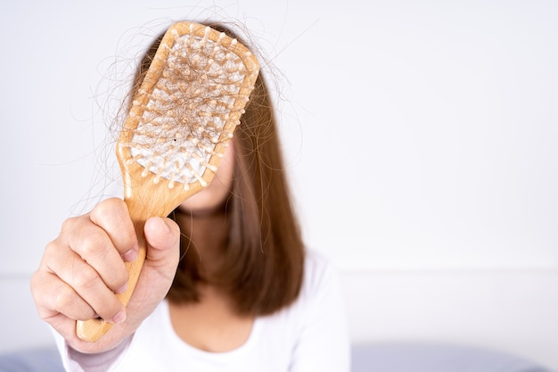 Closeup hand holding comb and hair fall problem. Premium Photo