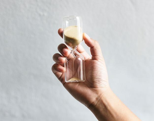 Closeup of hand holding hourglass Premium Photo