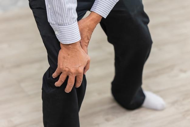 Крупным планом рука старшего человека боли в колене. Premium Фотографии