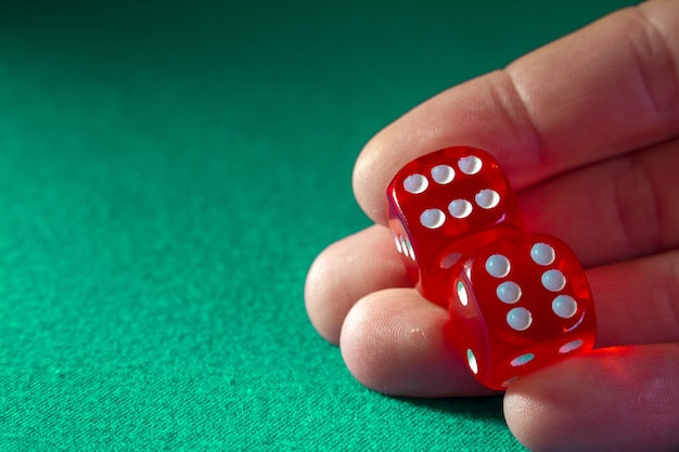Closeup of hand holding red dice with a winning combination on green cloth in a casino. Premium Photo
