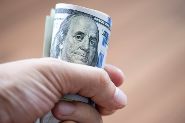 Closeup of hand holding roll of us dollar banknote for paying someone Premium Photo