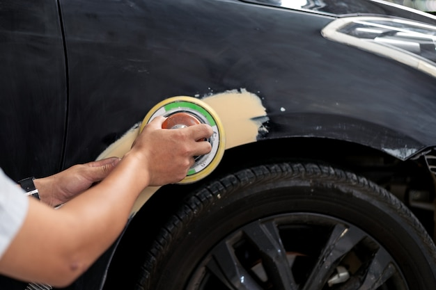 Крупным планом ручной механик работника шлифовальные полировки кузова  автомобиля и подготовка к покраске на станции обслуживания. Подготовка к покраске автомобиля: шлифование и обезжиривание транспортного средства