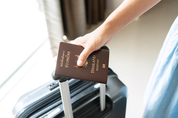 Крупным планом рука молодого азиатского путешественника, держащего паспорт в гостиничном номере. концепция праздника Premium Фотографии