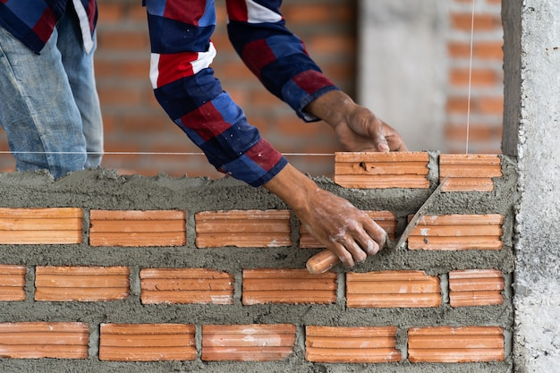 Closeup hand professional construction worker laying bricks in new industrial site Premium Photo