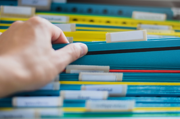 Closeup of a hand search and select a file folder Premium Photo