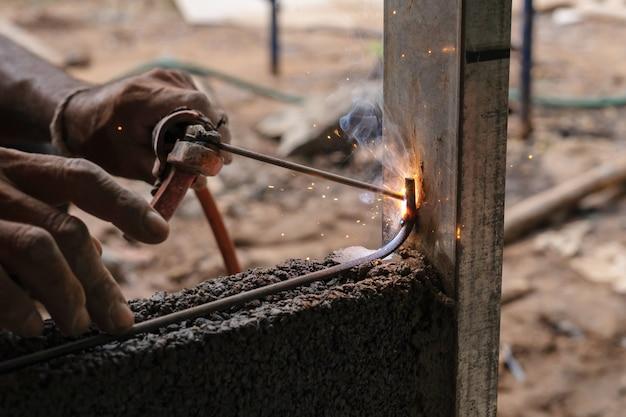 Крупным планом ручной сварки металла в строительной площадке Premium Фотографии