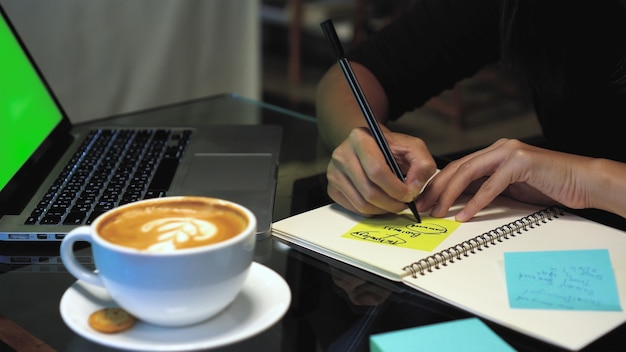 Closeup hands of asian businesswoman working and writing on paper notes over the notebook Premium Photo
