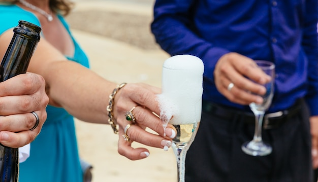 Closeup hands of the bride and groom with glasses of champagne wedding champagne glasses Premium Photo