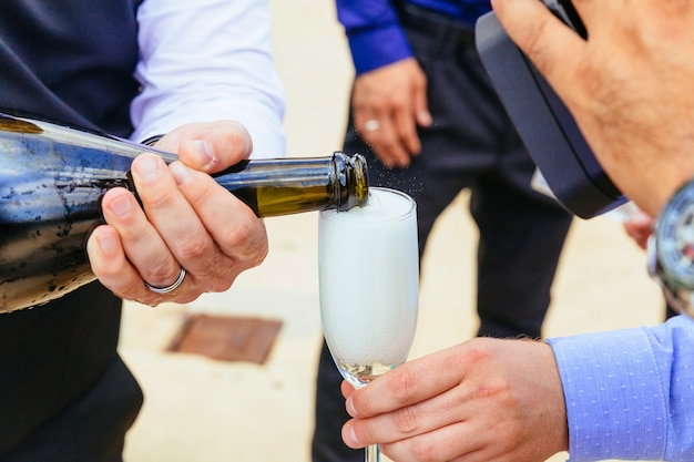 Closeup hands of the bride and groom with glasses  champagne Premium Photo