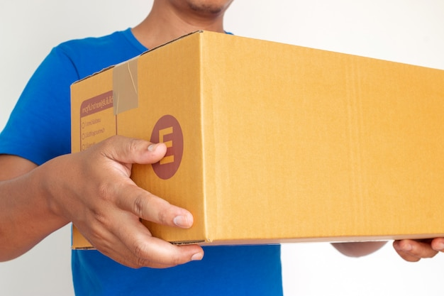 Closeup hands of delivery man holding package to deliver Premium Photo