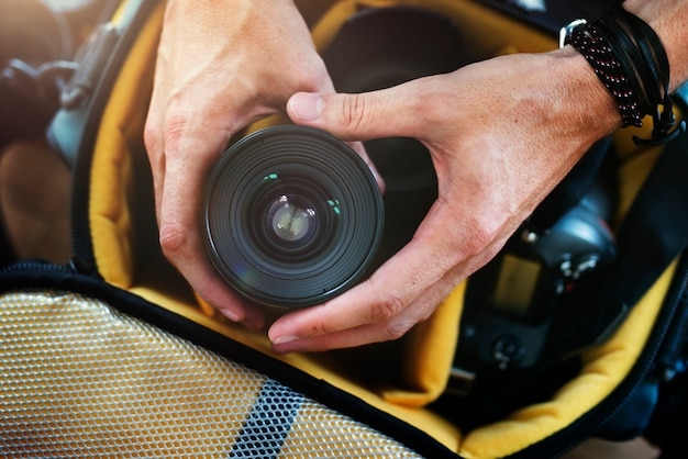 Closeup of hands getting camera lens from bag Free Photo