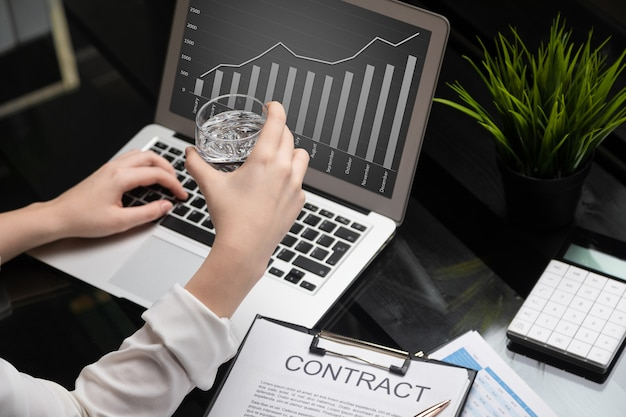 Closeup of hands holding glass of water and getting acquainted with the contract Premium Photo
