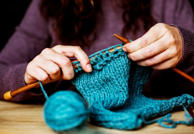 Closeup of hands knitting on wooden table Free Photo