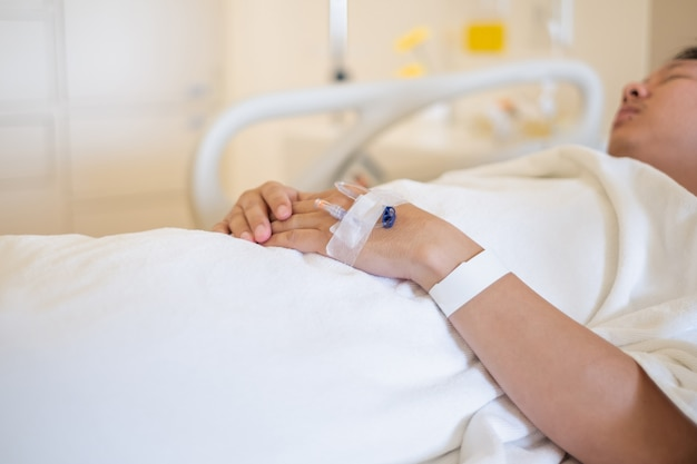 Closeup of hands with intravenous (iv) man patient in hospital bed. Premium Photo